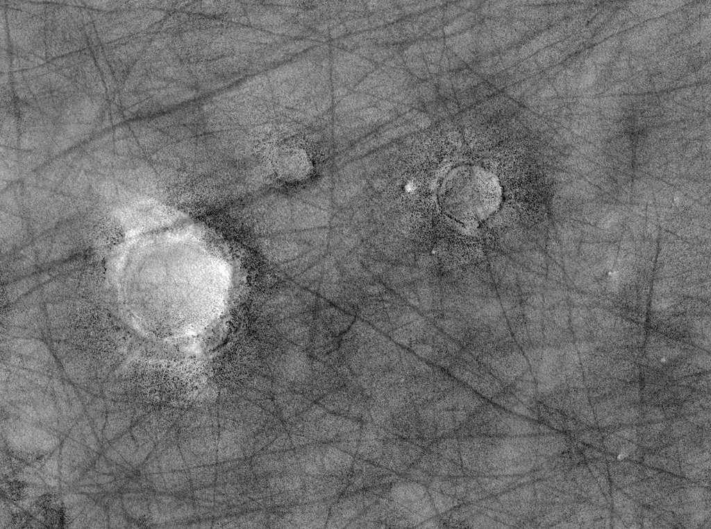 La caméra HiRise a photographié cette région située au nord d'Utopia Planitia. Les rainures sombres sont de simples ondulations. On distingue une différence de nature des terrains autour des cratères d'impacts. Un traitement approprié de l'image (voir ci-dessous) révèle des champs de rochers. Crédit Nasa / JPL-Caltech / University of Arizona