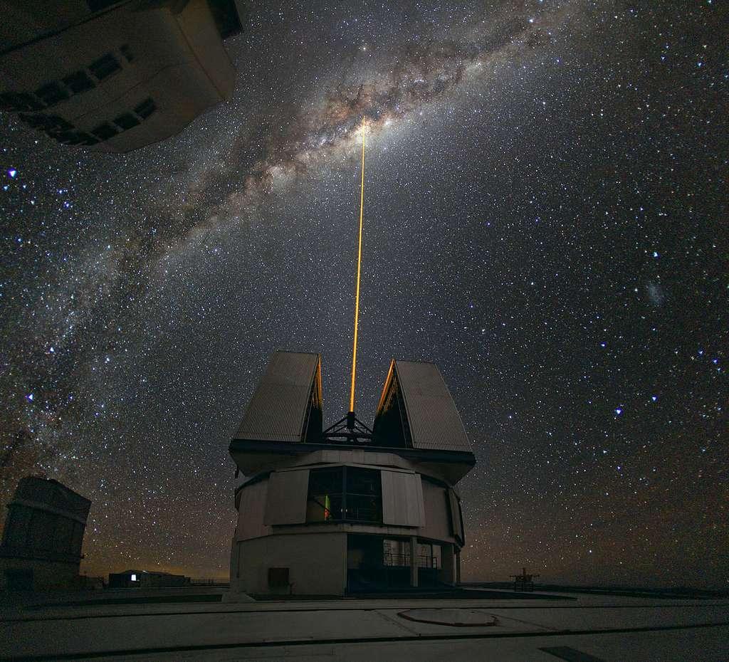 Rayon laser émis depuis un observatoire en direction du centre de la Voie lactée pour en étudier les détails. Le laser provoque la formation d'une « étoile artificielle » dans la mésosphère, à 90 km d'altitude. Cette source de lumière est utilisée comme référence pour compenser les turbulences atmosphériques. Le laser est réglé sur la fréquence d'excitation du sodium. Sa couleur jaune rappelle d'ailleurs celle des lampes à sodium utilisées dans l'éclairage urbain. Cette couche de sodium dans la mésosphère serait une trace laissée par les météorites qui la traversent. Cette méthode permet d'analyser les détails fins du ciel, tels que l'activité du trou noir se trouvant dans le centre galactique. Photo prise au grand angle (180°) à la mi-août 2008, près du Very Large Telescope, sur le Cerro Paranal, au Chili. © ESO, Yuri Beletsky, CC by 3.0
