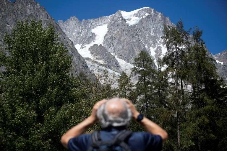 Un homme observe avec des jumelles le glacier de Planpincieux à Courmayeur, le 6 août 2020 au Val Ferret, en Italie. © Marco Bertorello, AFP