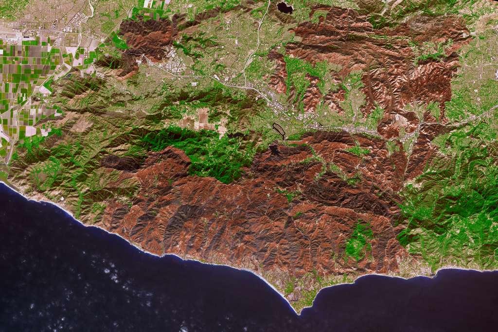 La cicatrice laissée par le « Woolsey Fire » vue par le satellite Terra de la Nasa le 18 novembre. Sur cette image infrarouge, les couleurs ont été accentuées pour avoir une apparence naturelle : la végétation brûlée apparaît en marron, celle indemne est verte. © Nasa Earth Observatory, Joshua Stevens, Nasa/GSFC/METI/ERSDAC/JAROS, US/Japan ASTER Science team