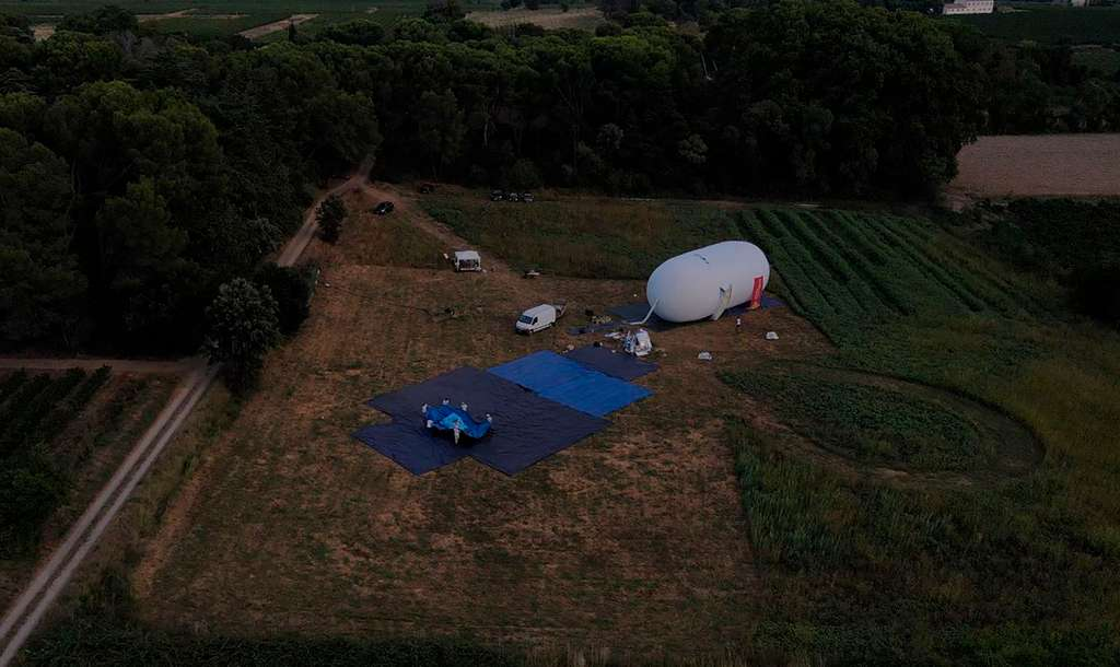 Cette photo montre le ballon régulateur gonflé et l'équipe du projet qui est en train de positionner le ballon porteur. La chaîne de vol totale fait 70 mètres de haut. © Zephalto