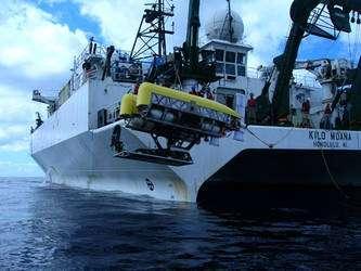 Le Nereus avant une plongée, mis à l'eau depuis le Kilo Moana, un navire basé à Honolulu (cliquer sur l'image pour l'agrandir). Ce Rov pèse trois tonnes et mesure 4,25 mètres de longueur pour 2,3 de large. Il est relié au navire par un long câble en fibre de verre protégée par une couche de plastique. Fin comme un cheveu, il mesure 40 kilomètres de longueur. Un câble en acier, trop lourd, se briserait sous son propre poids. Cette fibre optique sert à transmettre les commandes et, dans l'autre sens, à envoyer les images des caméras du bord. Dans l'eau, le Nereus est allégé par des flotteurs (qui jouent le rôle du ballon dans un dirigeable) constitués d'environ 800 sphères creuses de 9 centimètres de diamètre. La propulsion électrique et l'électronique sont alimentées par 4.000 batteries lithium-ion. © Matt Heintz, Woods Hole Oceanographic Institution