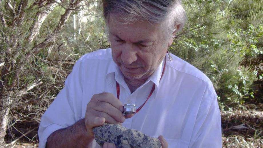 Andrew Glikson examine un échantillon de suévite, une roche formée par l'impact d'une météorite sur Terre. Il s'agit d'une brèche d'impact présentant des fragments de roche liés dans une matrice. © D. Seymour