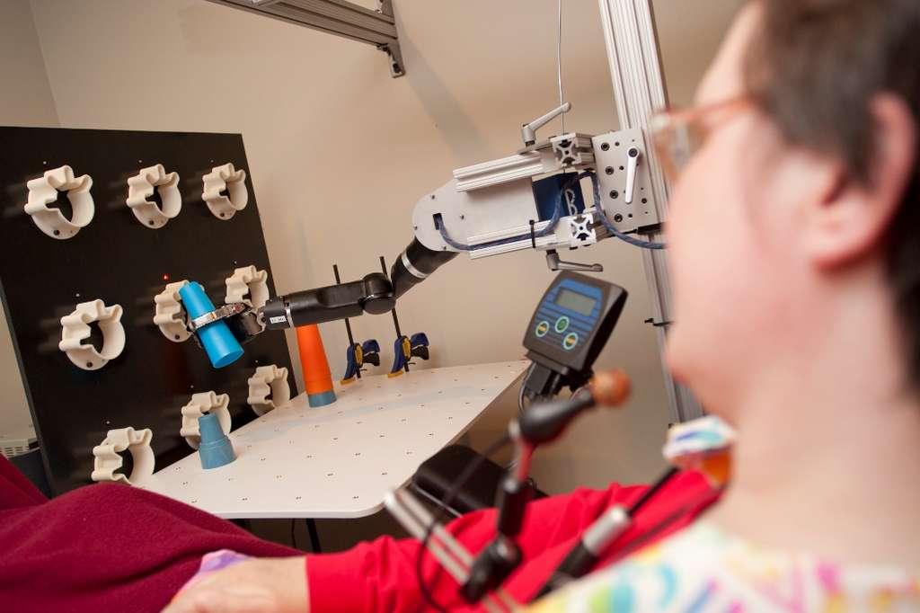 La patiente tétraplégique s'entraîne à déposer des plots les uns sur les autres avec son bras robotisé. Sa dextérité ne cesse de s'améliorer. © UPMC