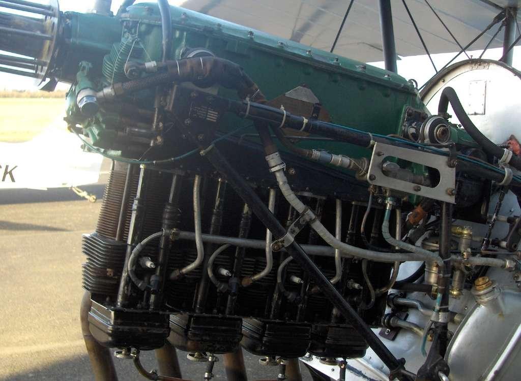 Une idée ancienne : sur ce vénérable moteur Renault 4PO3 équipant un biplan Stampe&Vertongen SV4C et qui fonctionne sans batterie, le démarrage est assuré par l'injection d'air comprimé dans les cylindres. En haut à gauche (au-dessous du boulon bleu), on remarque le compresseur, peint en vert, reconnaissable à ses ailettes de refroidissement. Entraîné par l'arbre moteur, il envoie l'air dans la bouteille située à l'arrière (vers la droite). La commande du démarreur libère la pression dans un système de distribution (sous le boulon bleu) qui l'envoie successivement vers chacun des quatre cylindres par les tuyaux d'aluminium verticaux et coudés, bien visibles. La conception remonte aux années 1930. Aujourd'hui, le contrôle électronique des soupapes permet d'aller plus loin et de faire fonctionner le moteur en associant les explosions et l'air comprimé. © Alain Deselle