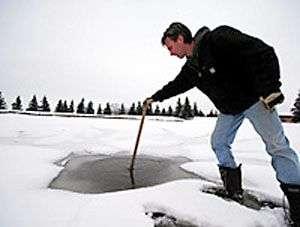 Le trou (déjà partiellement gelé) creusé par la météorite dans la glace recouvrant l'étang du terrain de golf de Spruce Grove. Crédit : The Sun