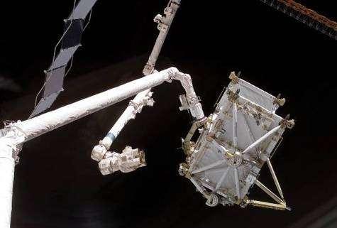 Transfert de la portion de poutre P5 depuis la soute de Discovery et l'ISS. L'élément passe ainsi du bras robotisé Canadarm de la navette à son homologue Canadarm 2 de l'ISS, une véritable poignée de mains en orbite ! Crédit NASA.