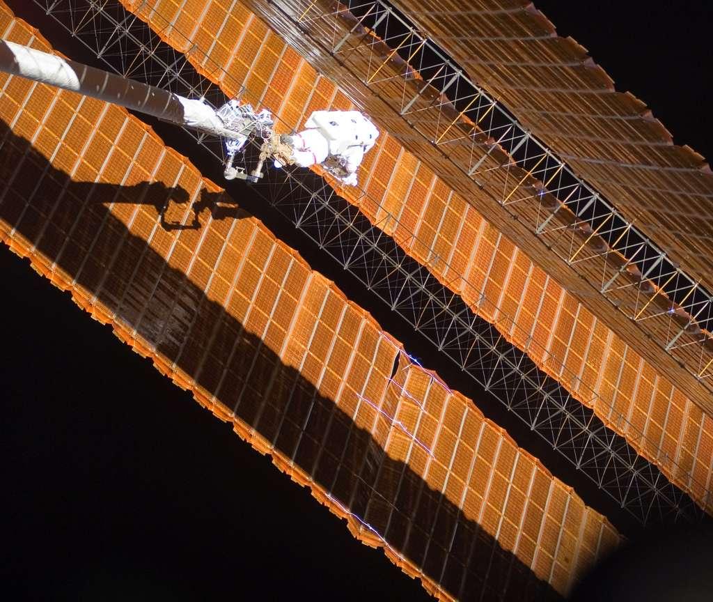 Scott Parazynski, lors de son intervention périlleuse pour réparer le panneau solaire déchiré (à droite). © Nasa