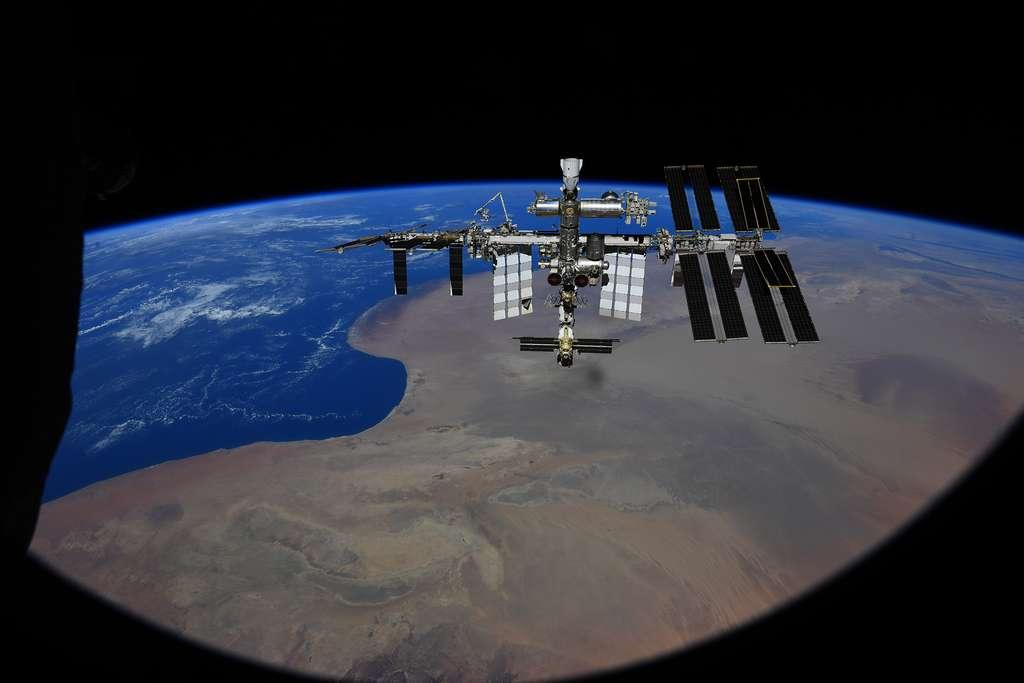 La Station spatiale internationale vue depuis l'hublot du véhicule Soyouz MS-18. On aperçoit clairement les panneaux solaires iRosa de dernière génération qu'ont notamment installés Thomas Pesquet et Shane Kimbrough. On peut aussi voir le bras robotique Canadarm-2, un Crew Dragon de SpaceX (tout en haut) et Nauka (tout en bas), le dernier module installé à l'ISS. © Roscosmos, P. Dubrov