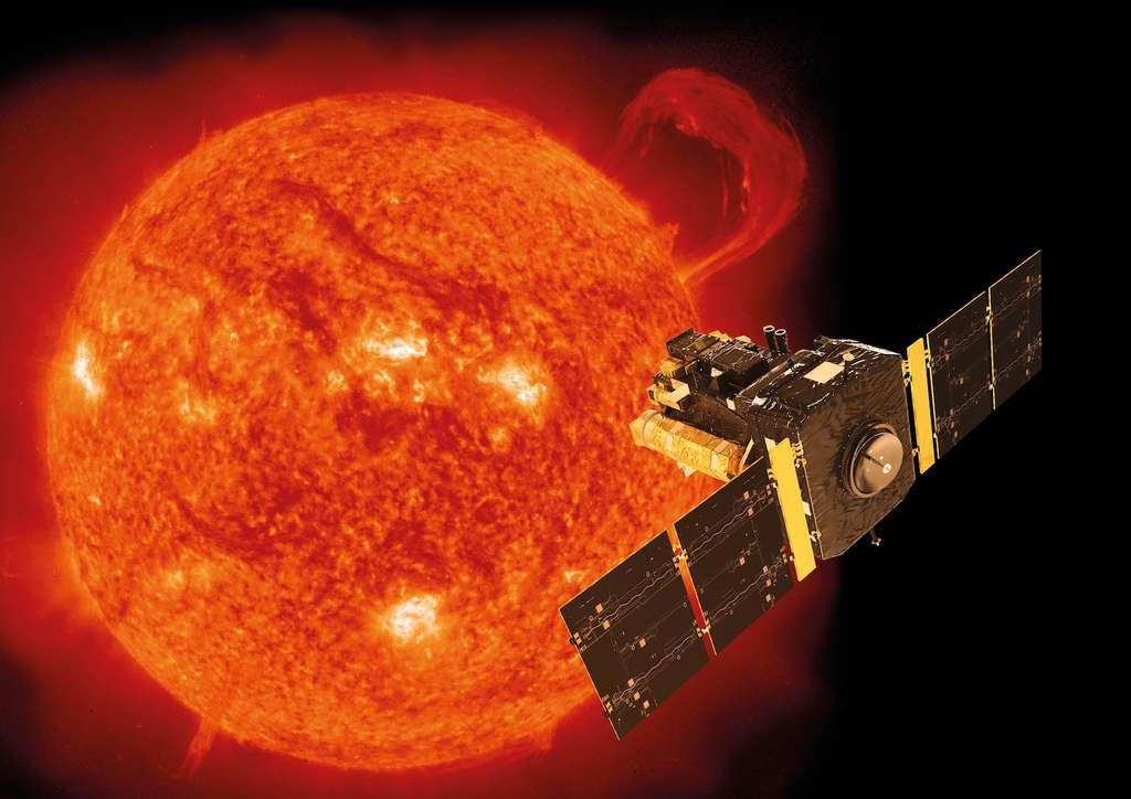 Illustration de Soho superposée à une image de notre étoile prise par le satellite le 14 septembre 1999 avec l'instrument EIT (Extreme-ultraviolet Imaging Telescope). Ce jour-là, une gigantesque protubérance en forme de poignet se développait sur le limbe du Soleil. Le pic d'activité du cycle 23 allait alors débuter. © Soho, Esa, Nasa, ATG medialab