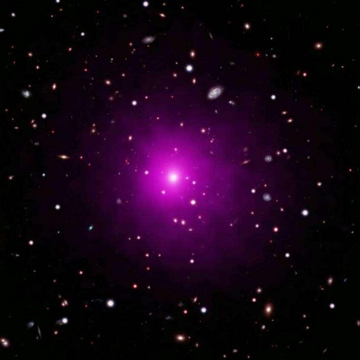 Un trou noir devrait se trouver dans l'énorme galaxie au centre de l'amas de galaxies Abell 2261, situé à environ 2,7 milliards d'années-lumière de la Voie lactée. Cette image composite d'Abell 2261 contient des données dans le visible, prise par Hubble et le télescope Subaru, montrant des galaxies dans l'amas en arrière-plan, et des données en rayons X de Chandra montrant des gaz chauds (de couleur rose) envahissant l'amas. Au centre de l'image, on voit la grande galaxie elliptique au centre de l'amas. © Nasa