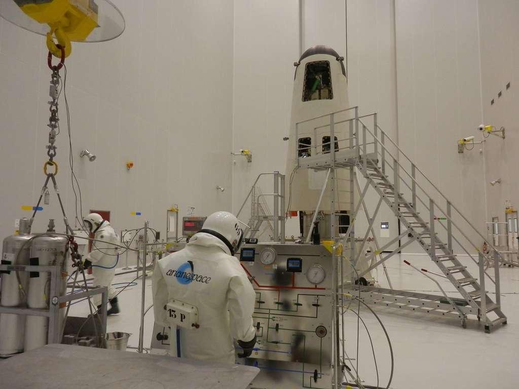 Deux ergoliers remplissent l'IXV d'hydrazine, un carburant très toxique pour la santé humaine. © Esa, Cnes, Arianespace