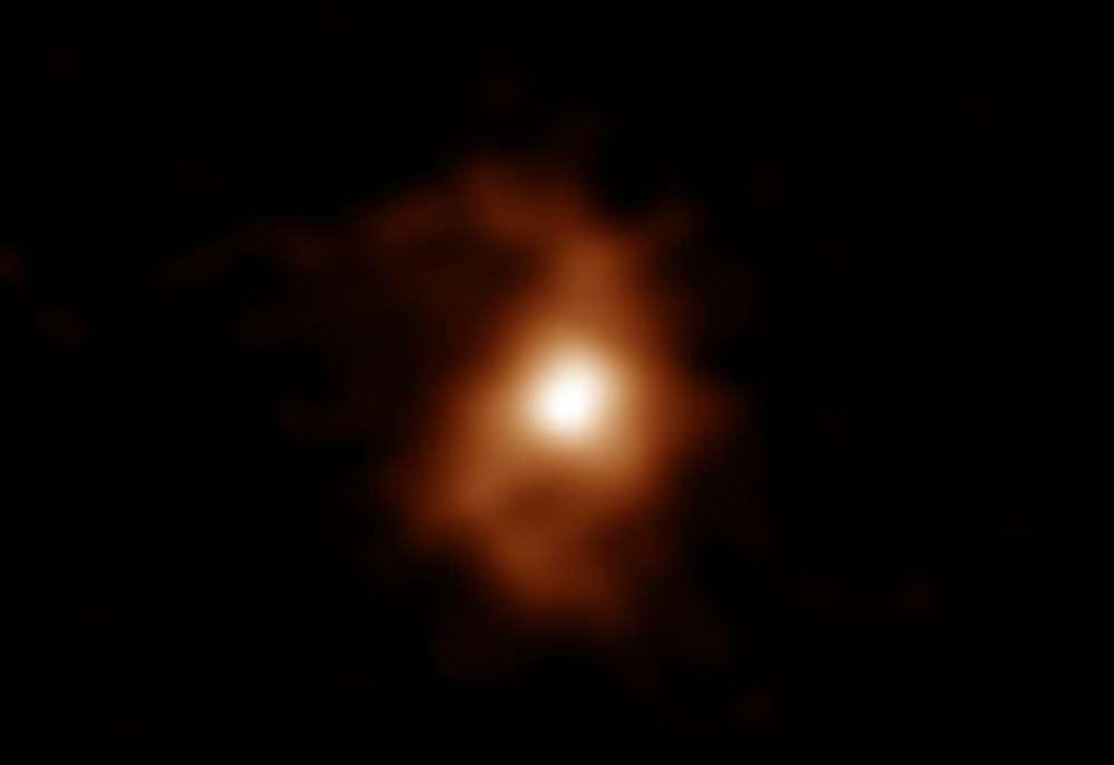 Voici en fausses couleurs une image d'Alma de la galaxie BRI 1335-0417 il y a 12,4 milliards d'années. Alma a détecté les émissions d'ions carbone dans la galaxie. Les bras en spirale sont visibles des deux côtés de la zone compacte et lumineuse au centre de la galaxie. Le décalage vers le rouge de cet objet est z = 4,41. C'est en utilisant les paramètres cosmologiques mesurés avec le satellite Planck (H0 = 67,3 km / s / Mpc, Ωm = 0,315, Λ = 0,685: Résultats Planck 2013) que nous pouvons calculer sa distance. © Alma (ESO/NAOJ/NRAO), T. Tsukui & S. Iguchi