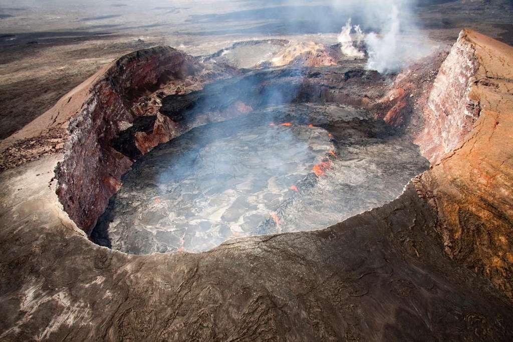 Vue aérienne du lac de lave perché dans le cratère de Pu'u O'o. De petites fluctuations du niveau du lac de lave entraînent de fréquents débordements. Ceux-ci servent à construire la digue autour du lac encore plus haut, amplifiant l'aspect perché. © Hawaiian Volcano Observatery USGS, wikimedia commons, DP