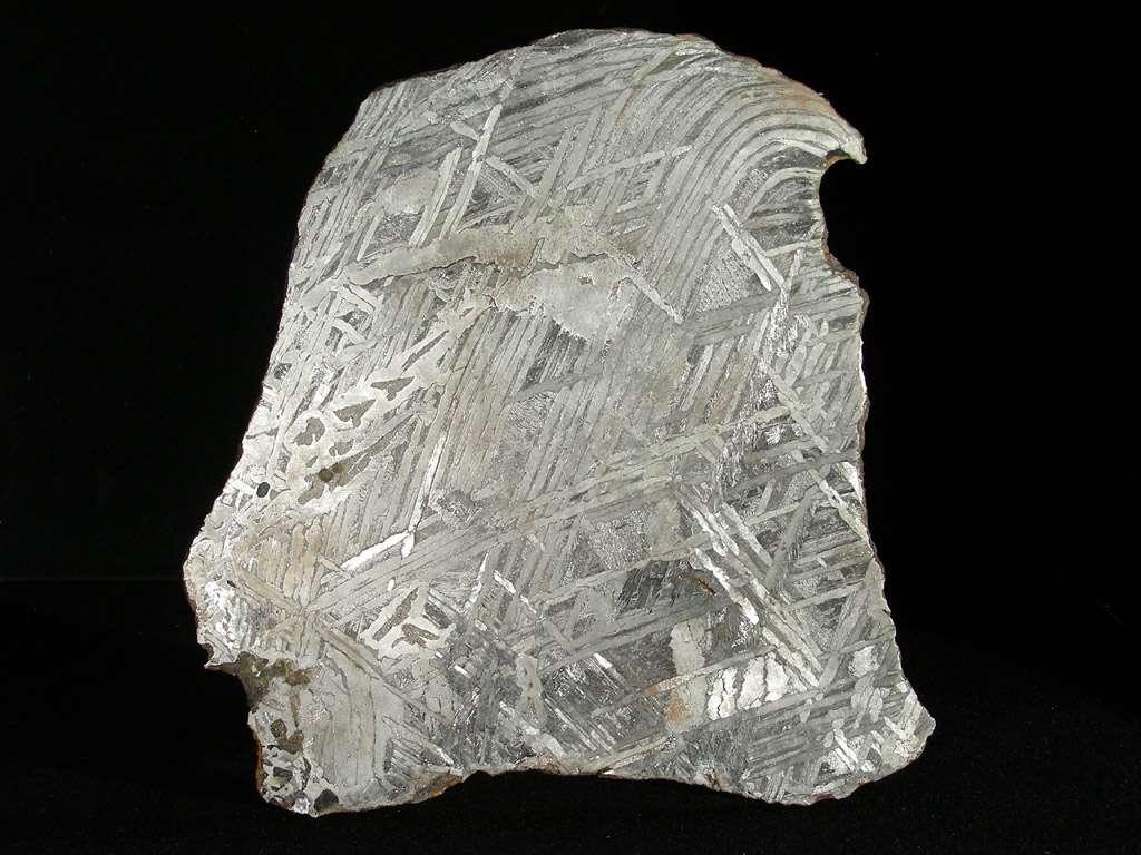 On voit ici la structure caractéristique des météorites riches en fer et nickel dites Widmanstätten lorsqu'elles sont attaquées à l'acide. Ces sidérites sont des fragments d'astéroïdes qui eux-mêmes sont riches en métaux, dont le précieux platine. © L. Carion-www.carionmineraux.com