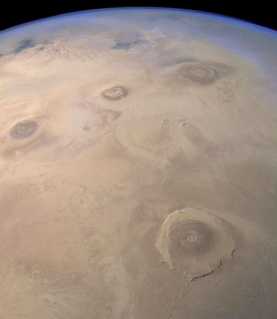 Vue contemporaine de l'ensemble qui constitue le dôme de Tharsis, immense renflement de 5.000 km de diamètre. On distingue notamment le mont Olympe (21 km d'altitude) et le trio de la chaîne de Tharsis : Ascraeus (environ 18 km), Pavonis (14 km) et Arsia (17,7 km). On aperçoit vers le limbe, le Labyrinthe de la nuit, où s'ouvre la grande Valles Marineris. L'image a été prise par la sonde Mars Express, le 29 juin 2014. © Esa, DLR, Fu Berlin, Justin Cowart