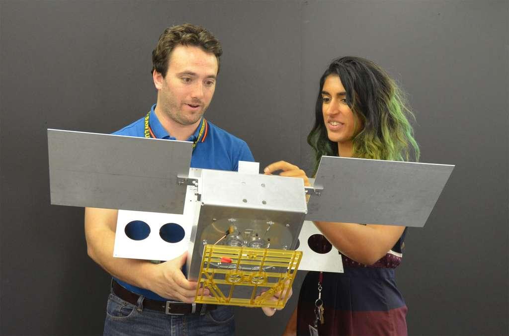 Deux des ingénieurs du projet MarCO, Joel Steinkraus et Farah Alibay, tenant dans leurs mains une maquette à l'échelle 1 d'un des deux CubeSat de MarCO. © JPL, Nasa