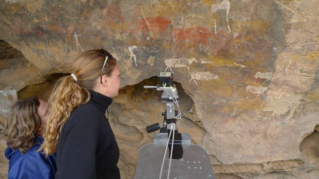 Devant le motif peint a été installée la tête du spectromètre Raman, sur un dispositif à déplacement micrométrique porté par un pied d'appareil photo. La lumière laser (verte, 532 nm), amenée par une fibre optique, est focalisée à l'aide d'un objectif de microscope. La lumière réfléchie est reprise par le même objectif et dirigée vers une autre fibre optique reliée à l'appareil de mesure. © Luc Ronat/CNRS Photothèque