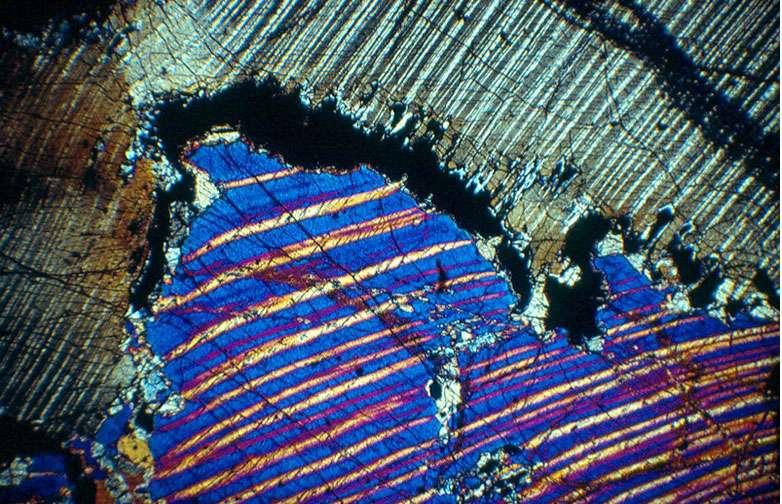 Ci-dessus, une pyroxénite à grenat et diamant graphitisé du massif des Beni Bousera (Maroc), provenant d'au moins 150 km de profondeur. Les textures sont liées au refroidissement et à la décompression. Cette lame mince (longueur 2 cm), a été observée en lumière polarisée analysée. © Jacques Kornprobst