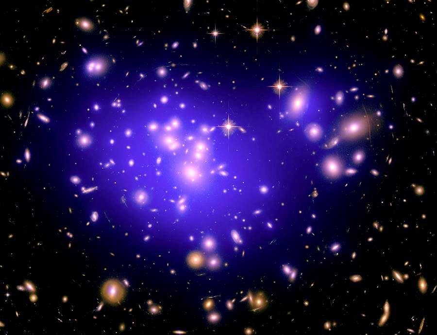 L'amas de galaxie Abell 1689 contient de la matière noire dont la distribution peut être déduite des effets de lentille gravitationnelle et être reconstituée à l'ordinateur. C'est ce qui a été fait sur cette image où l'on voit surimposée en fausse couleur violette la matière noire. © Nasa, Esa, E. Jullo (JPL/LAM), P. Natarajan (Yale) et J.-P. Kneib (LAM)