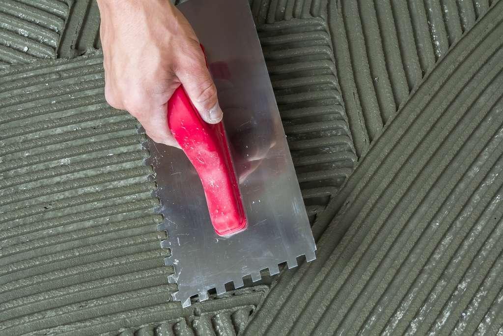 Étalez le mortier colle sur le sol et le travertin à l'aide d'un peigne à colle de 10 millimètres. © bilanol, Fotolia