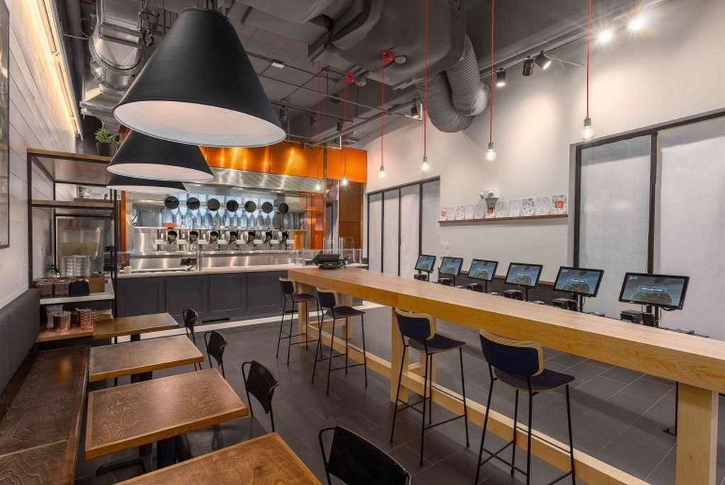 La cuisine du restaurant Spyce repose sur ses sept woks et sur un système de distribution des ingrédients robotisé. © Spyce