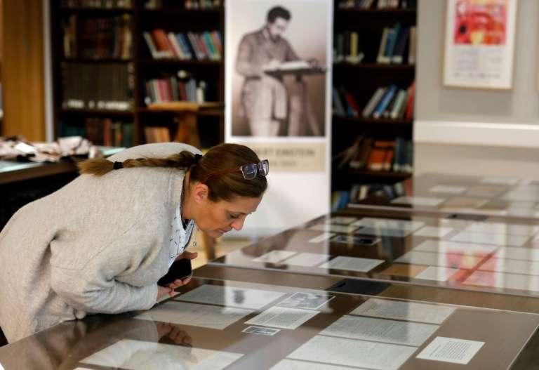 Une femme examine des pages manuscrites d'Albert Einstein exposées à l'université hébraïque de Jérusalem, le 6 mars 2019. © Menahem Kahana, AFP