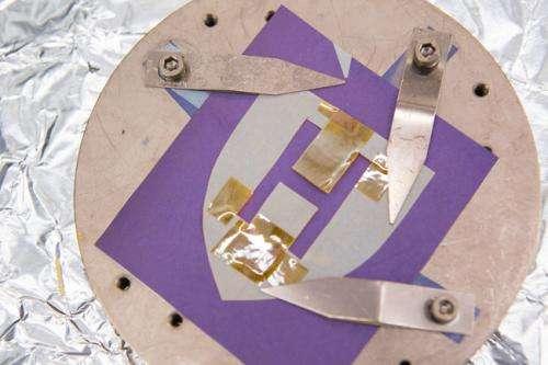 À la sortie de l'appareil, l'échantillon est revêtu d'une fine couche métallique. Le pochoir sur lequel le germanium s'est déposé directement est gris, comme la couleur naturelle du germanium. Le reste du papier, sur lequel le germanium s'est déposé sur la couche d'or, apparaît mauve.