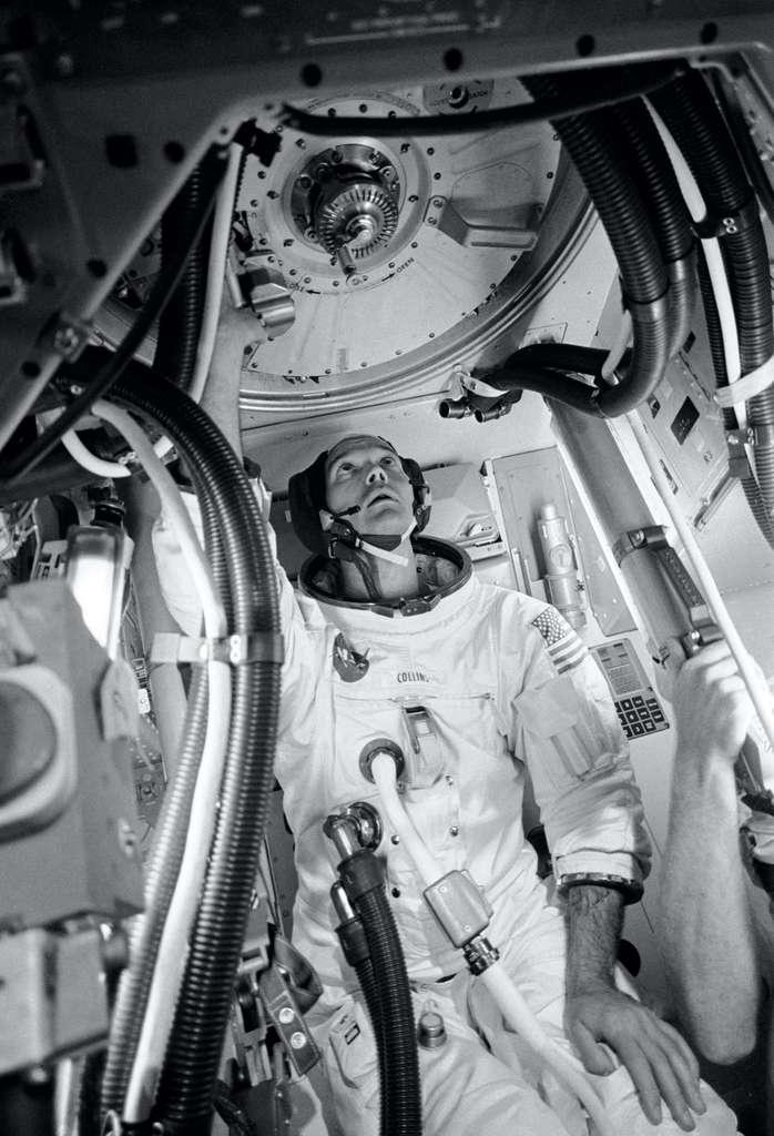 L'astronaute Michael Collins, pilote du module de commande du vol Apollo 11, à l'intérieur d'une maquette de ce module, pratiquant les procédures avec le mécanisme d'amarrage. Michael Collins se tient dans le tunnel d'amarrage qui fournit un passage vers et depuis le module lunaire. © Nasa