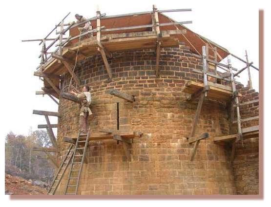Enlèvement des boulins par les charpentiers sur la tour de la chapelle. Les boulins sont les parties en bois perpendiculaires à la maçonnerie. Les boulins sont une partie des échafaudages montés sur les maçonneries. Une fois la maçonnerie réalisée, les boulins sont démontés pour, le cas échéant être remontés sur un étage supérieur. A côté du charpentier du bas : archère. © Photo Guédelon.