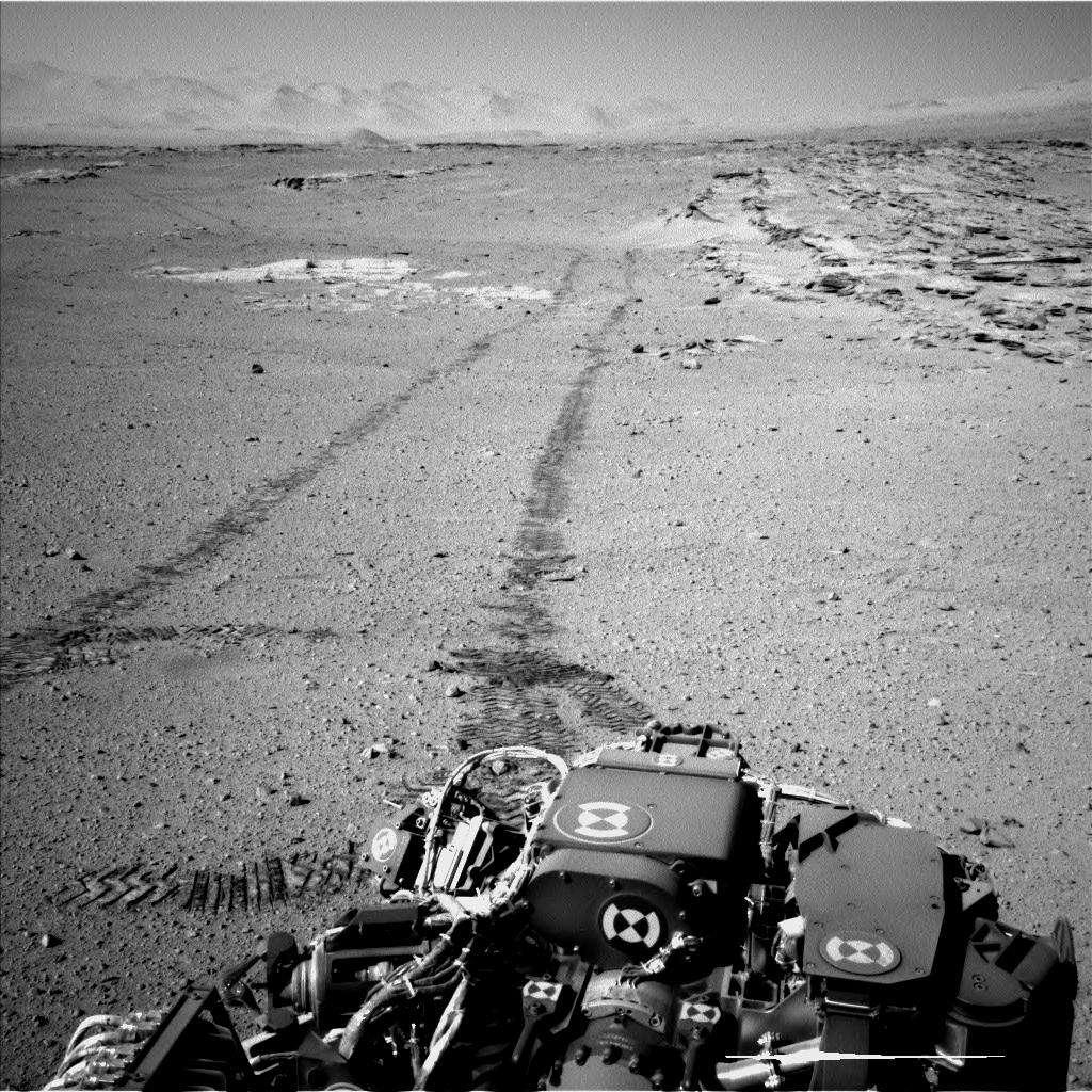 Image prise le 19 février, lors du 548e jour de Curiosity sur Mars. Après avoir profité du panorama où le mont Sharp écrase l'horizon, le rover a repris la route, toujours en marche arrière. À droite, on reconnaît les alignements de roches du site nommé Junda, où il a fait une pause quelques instants plus tôt. À l'arrière-plan, on distingue les remparts qui bordent le vaste cratère Gale. © Nasa, JPL-Caltech