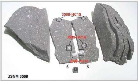 Figure 1. Un échantillon de la météorite d'Allende, une chondrite carbonée CV3, sciée en plaques d'environ 1 cm d'épaisseur (le cube marqué de la lettre T, de 1 cm de côté, donne l'échelle). Des inclusions réfractaires CAIs (Ca, Al-rich inclusions en anglais) ont été identifiées, comme ici, signalées en rouge sur les plaques 5 et 6. © University of Maryland