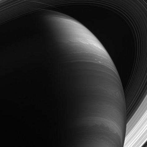 Le savoir de Saturne. Saturne offre des mystères bien plus profonds et une histoire bien plus étonnante que son homologue de l'antiquité. Ses paysages gazeux semblent se modifier au gré des observations. Ses ouragans, ses orages titanesques grondent sans répit et ses anneaux majestueux content une éternité de collisions et de cataclysmes, tandis que ses satellites recèlent peut-être les secrets des prémisses de la vie. Position de Cassini : 28° d'inclinaison sud par rapport au plan des anneaux. Image infrarouge (890 nm). Date : 30 janvier 2007. Distance : 1,1 million de km.
