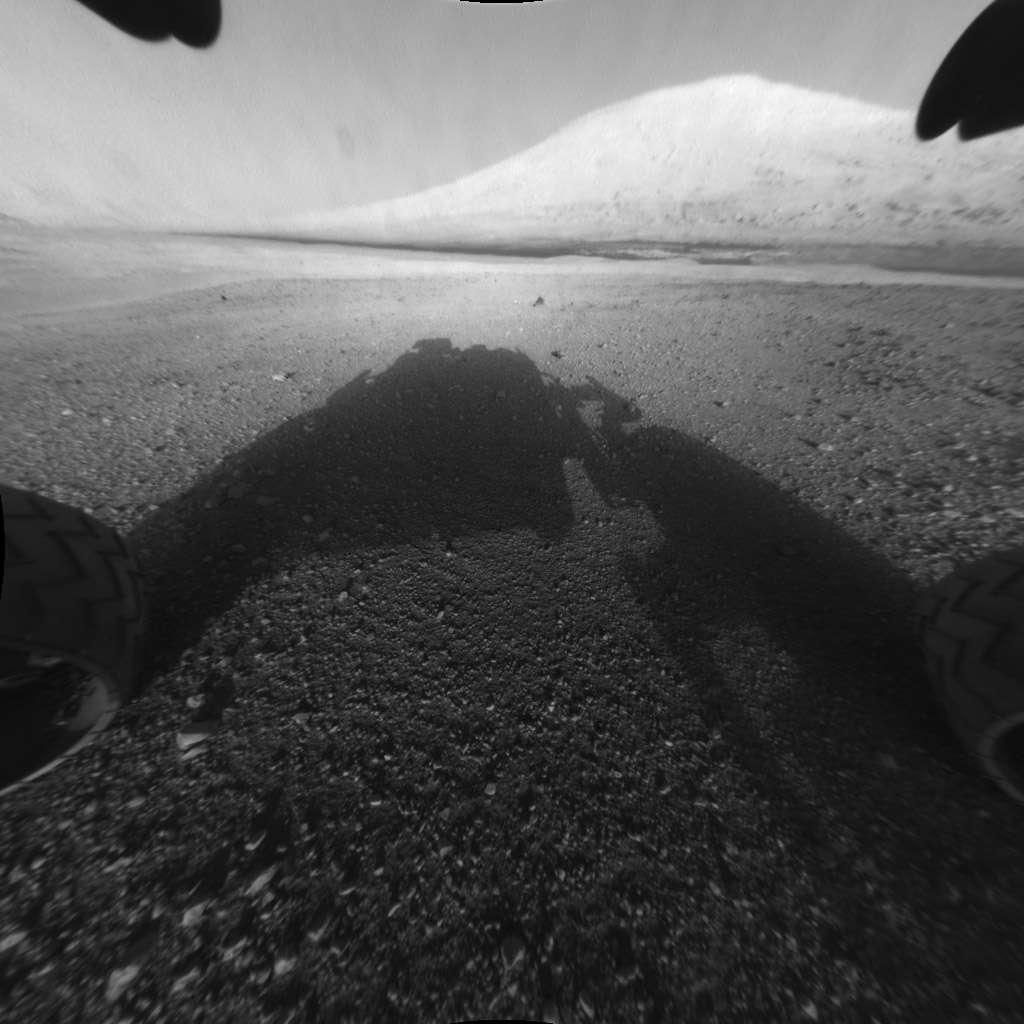 Le mont Sharp au-dessus de l'ombre du rover Curiosity. « Du haut de cette montagne, 3 milliards d'années nous contemplent... », doivent penser les planétologues. La photographie a été prise par l'une des 8 hazcams, (Hazard-Avoidance Cameras) qui filment en monochrome et serviront à repérer les obstacles alentour. Leur objectif est un fish-eye, c'est-à-dire un très grand angle et cette image a été retouchée pour redresser les perspectives. © Nasa, JPL-Caltech