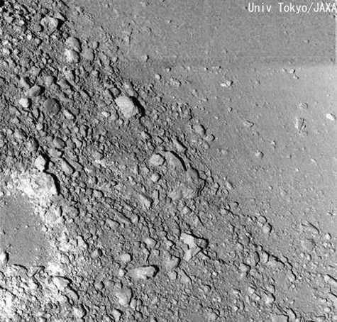 Sur cette image, on distingue très bien la nette séparation entre une zone lisse (à droite) et une zone où la poussière et les petits débris se sont infiltrés à travers les plus gros rochers, laissant ceux-ci à découvert (à gauche). Crédit Université de Tokyo / JAXA.