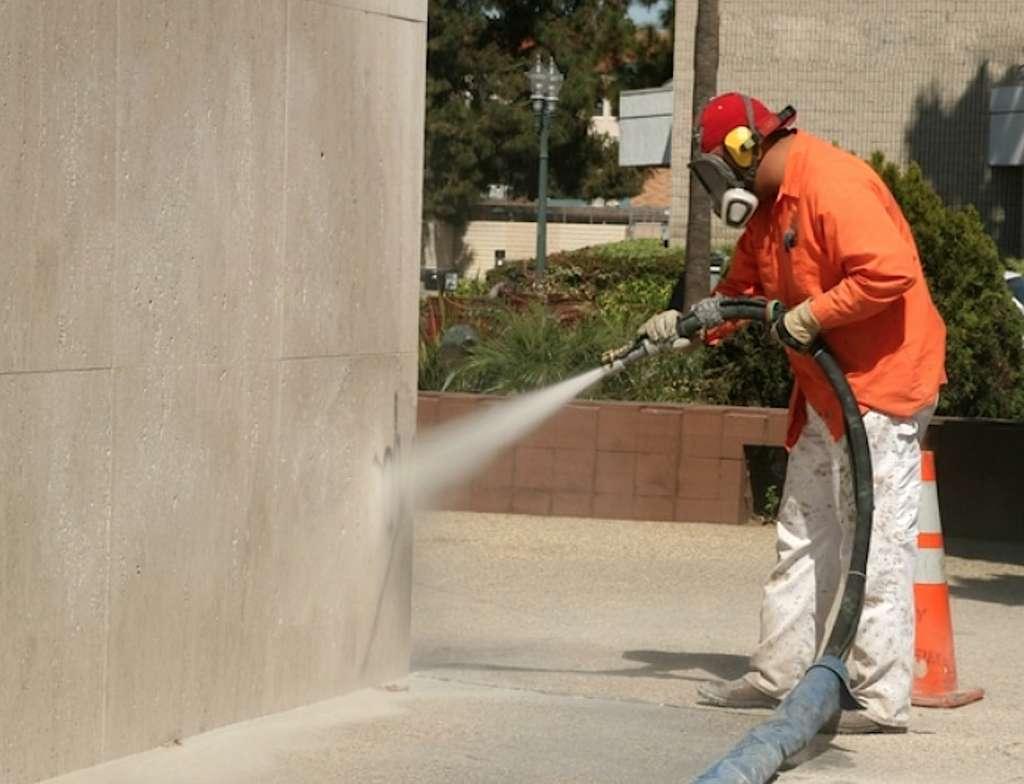 Maintenez la lance en biais, suivant un angle d'environ 40°. Ne l'approchez pas à moins de 20 centimètres de la façade. Opérez par passes régulières, de haut en bas. © cabine-de-sablage.net