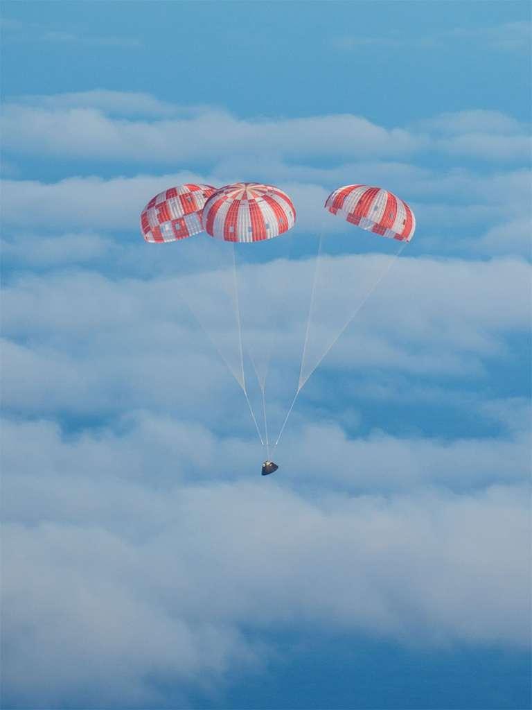 Retour sur Terre de la capsule Orion après son vol orbital. Les trois parachutes sont ici correctement déployés, dans une configuration idéale qui limite le ballant de la capsule. © Nasa