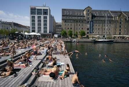 Bains de soleil et baignades devant le Théâtre national de Copenhague pendant un épisode de canicule, le 25 juillet 2019 au Danemark. © Liselotte Sabroe, Ritzau Scanpix, AFP
