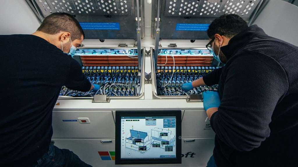 Deux ingénieurs inspectent l'intérieur du réservoir pour le refroidissement par immersion biphasée. © Gene Twedt pour Microsoft