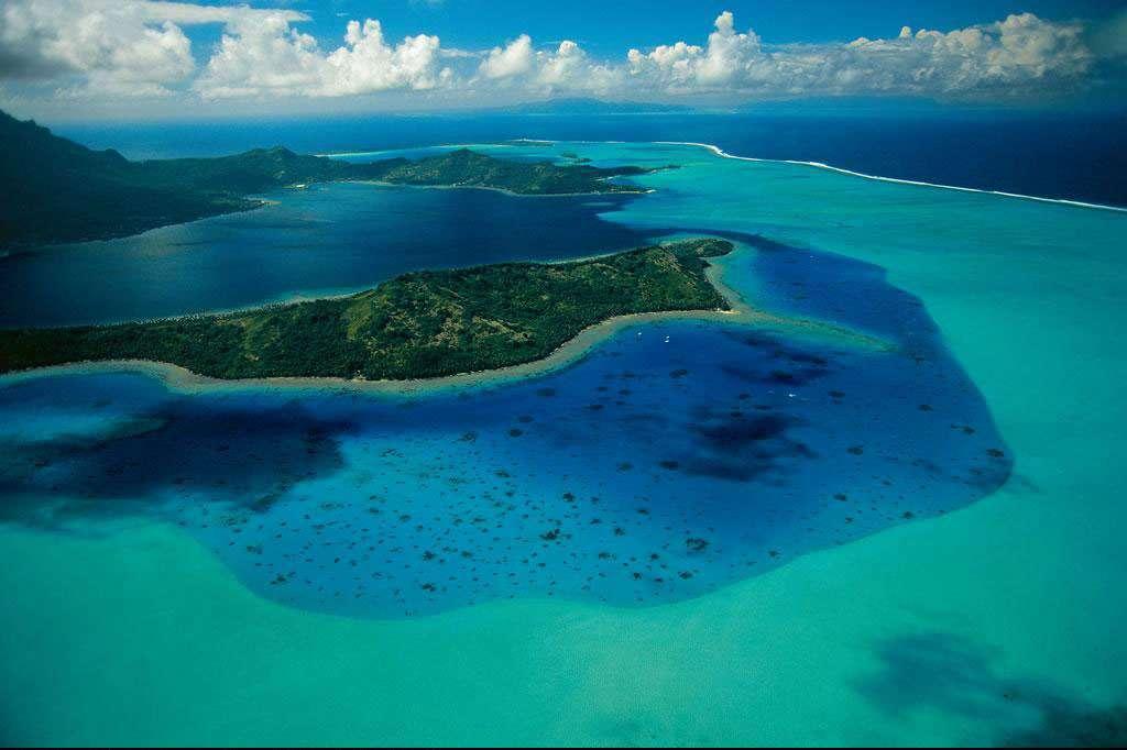 Bora Bora, Polynésie française, France (16°31' S - 151°46' O). L'archipel des Iles Sous-le-Vent, en Polynésie française, territoire d'outre-mer depuis 1946, abrite cette île de 38 km2 dont le nom signifie « la première-née ». Elle est constituée de la partie émergée du cratère d'un ancien volcan, vieux de 7 millions d'années, entourée d'un récif barrière de corail sur lequel se sont développés des îlots coralliens couverts d'une végétation comprenant principalement des cocotiers. © Yann Arthus-Bertrand - Tous droits réservés