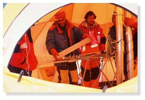 Ambiance de travail dans une des deux tentes de carottage : le carottier et la découpe de glace en carottes de 70 cm prêtes à être emballées dans leur gaine de plastique numérotée. Illimani, Bolivie. © IRD/Bernard Francou.