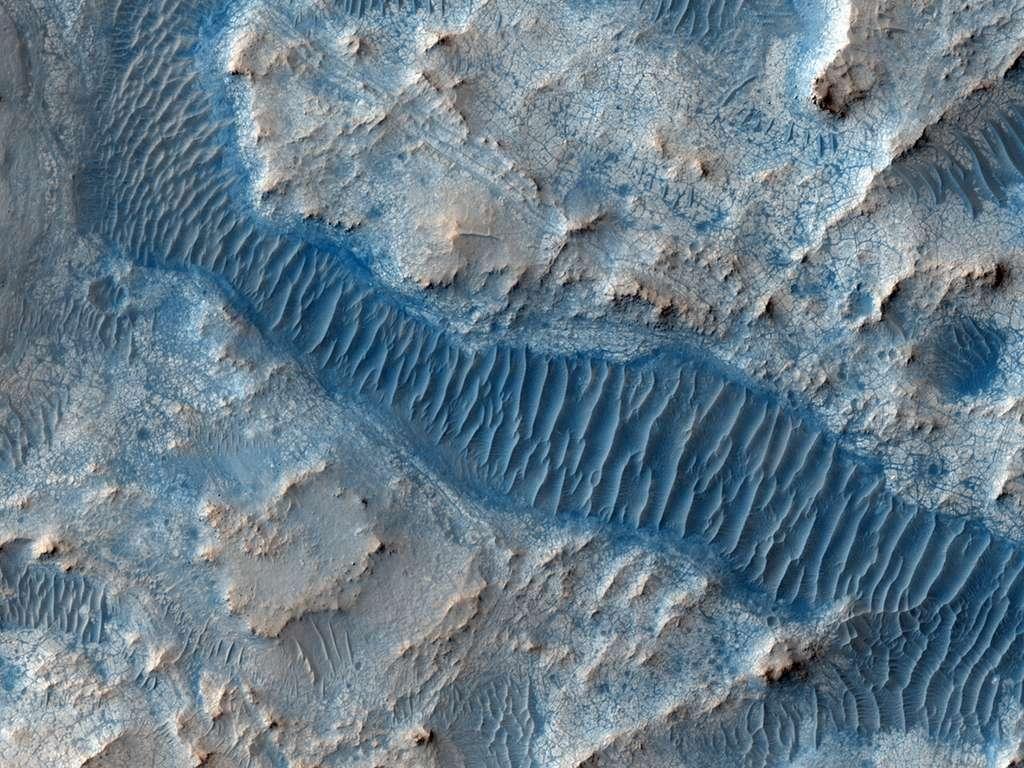 D'étonnants dépôts sédimentaires au fond d'une vallée se présentent sous forme de vagues figées. © Nasa/JPL/University of Arizona