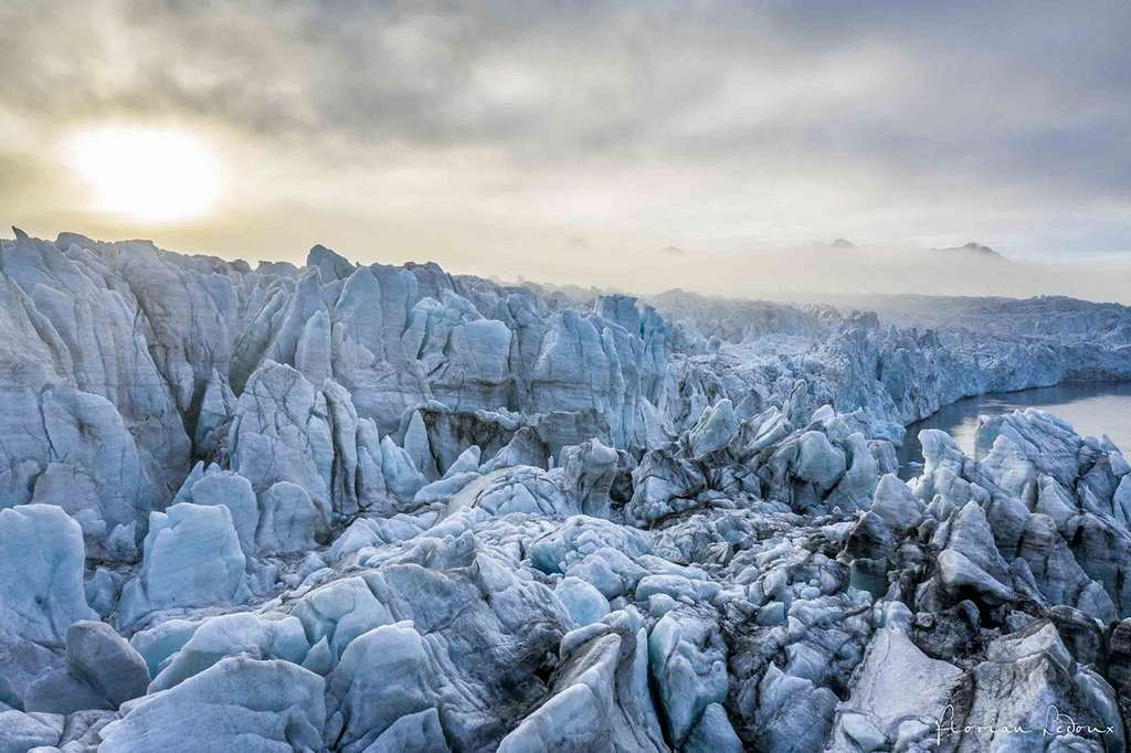 Vue au-dessus du glacier Olsokbreen dans le brouillard alors que le soleil de minuit perce. © Florian Ledoux, tous droits réservés