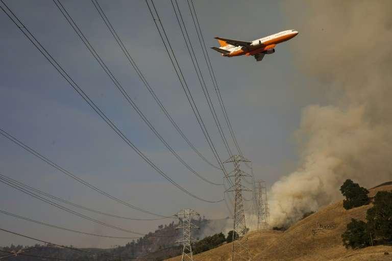 Un avion bombardier d'eau survole le Kincade Fire, le 26 octobre 2019 en Californie. © Philip Pacheco, AFP
