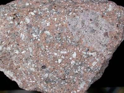 Sur cette image, la rhyolite est en blanc, le feldspath est en gris et le quartz constitue la matrice rose. © DR