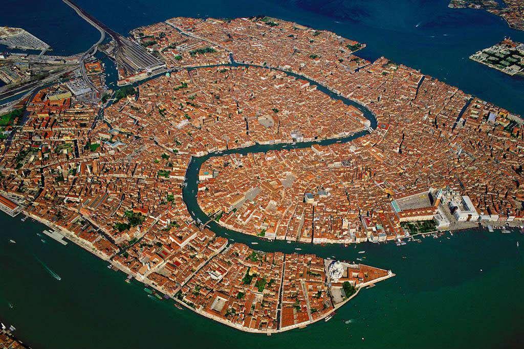 Vue générale de la ville de Venise, Vénétie, Italie (45°25' N - 12°45' E). Venise est un archipel de 118 îles, séparées par 160 canaux qu'enjambent plus de 400 ponts, située au centre d'une lagune séparée de la mer par un cordon littoral entrecoupé par trois passes. Sa principale artère, le Grand Canal, est bordée par une centaine de palais de la Renaissance et de l'époque baroque érigés par les riches marchands vénitiens. Ils témoignent de l'importance prise par ces commerçants quand Venise s'est ouverte sur le monde extérieur. © Yann Arthus-Bertrand - Tous droits réservés
