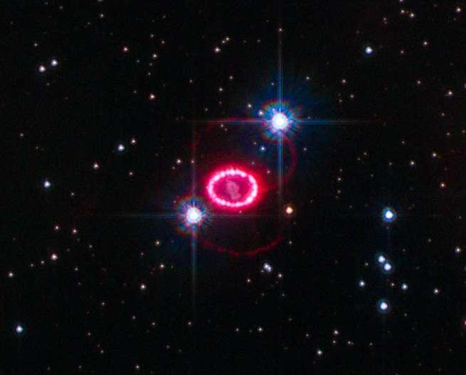 En rouge, rosé, le rémanent de la supernova SN 1987A, observe dans le Grand nuage de Magellan en 2010 par le télescope spatial Hubble. Les deux points brillants sont des étoiles d'avant-plan. © Nasa, ESA, K. France (University of Colorado, Boulder), et P. Challis et R. Kirshner (Harvard-Smithsonian Center for Astrophysics), Wikipedia, Domaine public