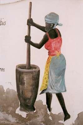 Peinture murale d'une femme pilant le mil. On note ici l'influence africaine. Du métissage important de l'île (colons portugais, esclaves capturés sur les côtes africaines) sont nés une culture et un peuple uniques. On fête le carnaval comme au Brésil, on s'habille à l'européenne, on porte les enfants sur le dos comme en Afrique. © IRD - Favier, Marie-Noëlle/ cap Vert, port de Santa Maria, île de Sal