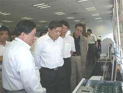 LI Guojie, directeur de l'Institut de technologie informatique montre le nouveau processeur au ministre de la Recherche et de la Technologie