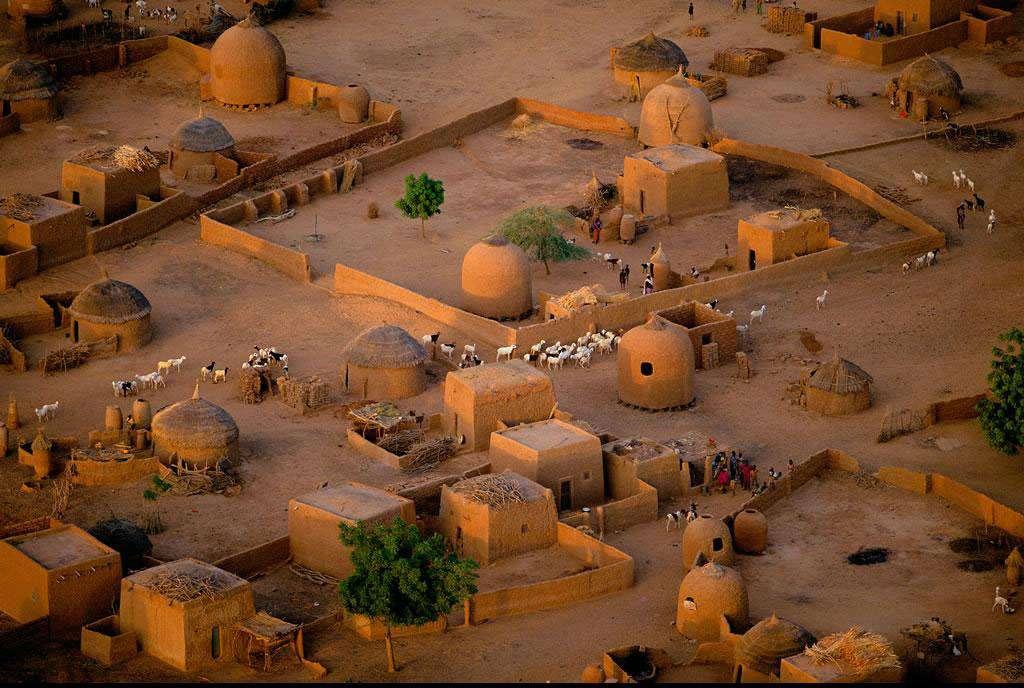Détail d'un village aux environs de Tahoua, Niger (14°50' N – 5°16' E). Ce village près de Tahoua, dans le sud-ouest du Niger, présente une architecture haoussa caractéristique, avec ses maisons cubiques en banco (mélange de terre et de fibres végétales) associées à d'imposants greniers à grain aux formes ovoïdes. Majoritaire dans le pays (54 % de la population), le peuple haoussa est essentiellement constitué d'agriculteurs sédentaires. © Yann Arthus-Bertrand - Tous droits réservés
